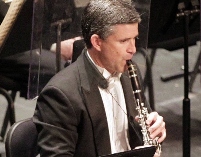 Image of Paul Votapek of the Naples Philharmonic on stage playing a clarinet during a performance