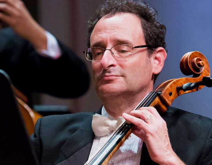 Image of Eric Dochinger of the Naples Philharmonic on stage playing cello during a performance