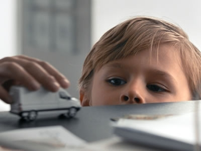 Image of a short child peering over his father's desk in a humorous manner, representing the Short category of films at the Naples International Film Festival