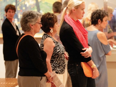 Image of patrons viewing art on the wall of the museum