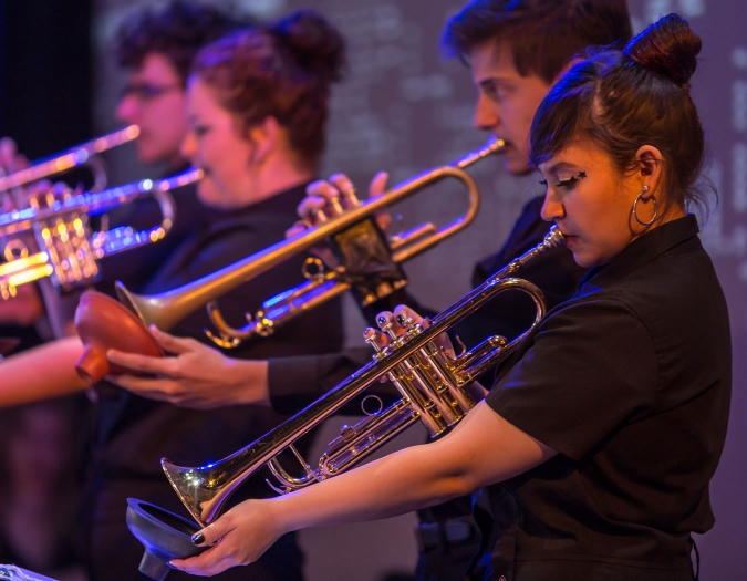 Image of student musicians performing on stage with the Naples Philharmonic Youth Jazz Orchestra