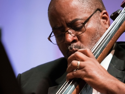 Image of Kevin G. Mauldin of the Naples Philharmonic on stage playing a bass during a performance