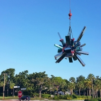 Image of Arik Levy's bold sculpture, RockGrowth 370 as it is carefully moved to its new home across Ridgewood Drive from Artis—Naples in Pelican Bay